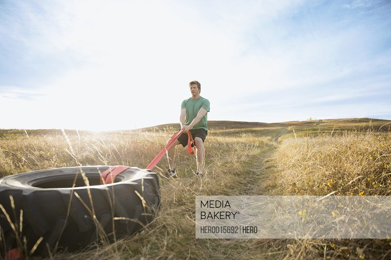 Man pulling crossfit tire in sunny rural field
