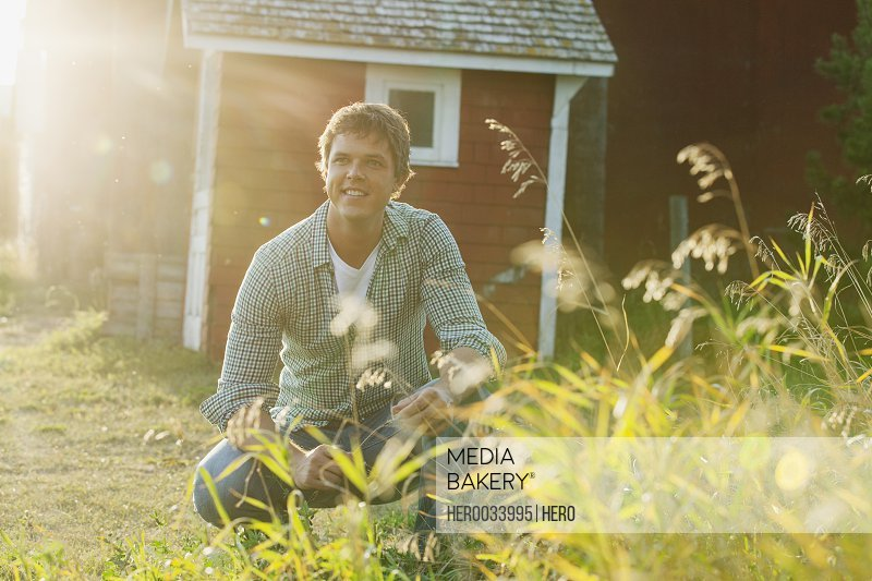 Mid adult man crouching on rural property.