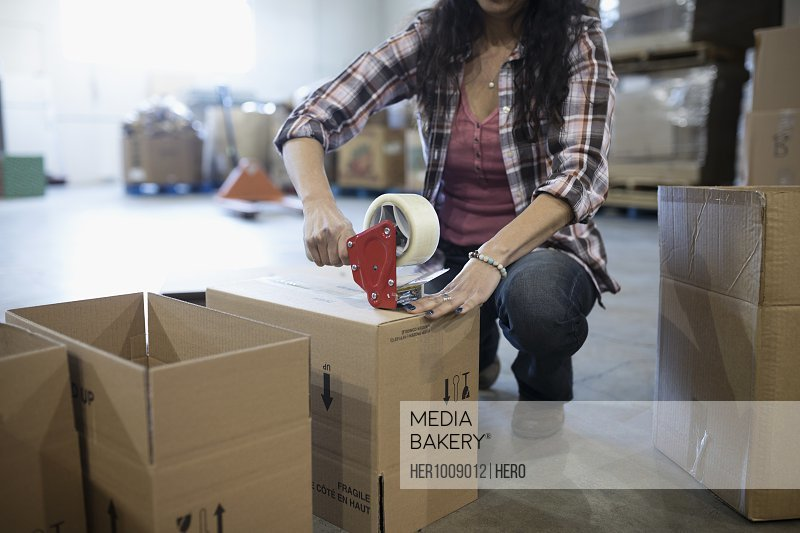 Female volunteer taping donation boxes in warehouse
