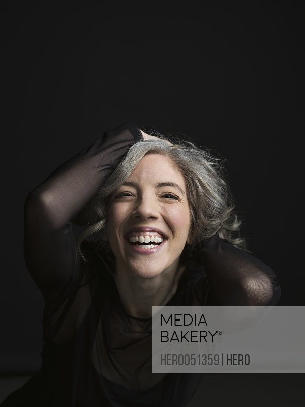 Portrait enthusiastic woman laughing with hands in hair against black background