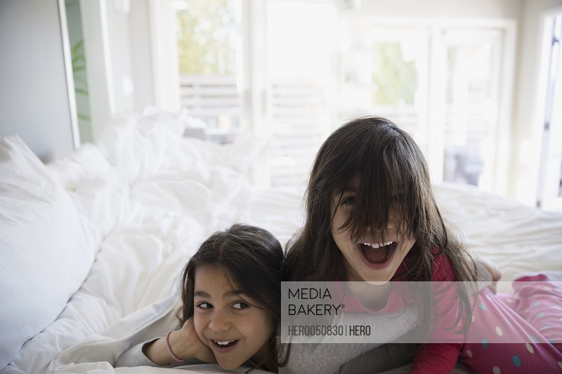 Portrait playful sisters laughing on bed