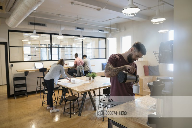 Architect pouring coffee at coffee pot in open plan office
