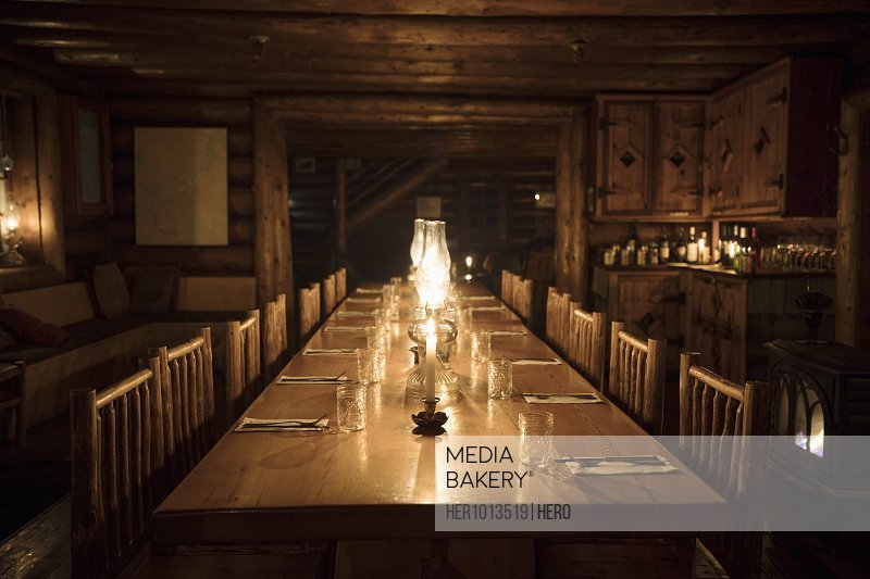 Gas lamps and candlelit rustic log cabin dining table
