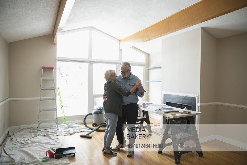 Romantic senior couple dancing, taking a break from painting living room, DIY