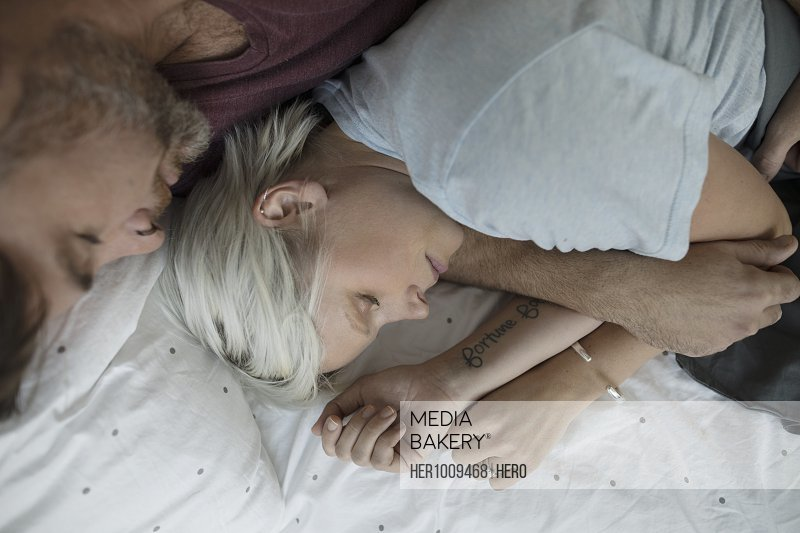 Overhead view affectionate, romantic couple sleeping and cuddling in bed