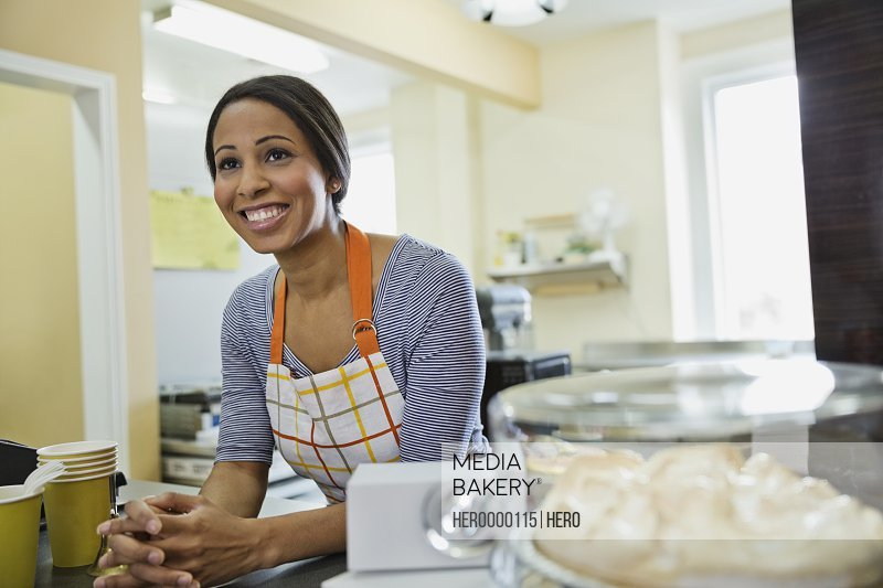 Smiling woman baker leaning on counter in bakery