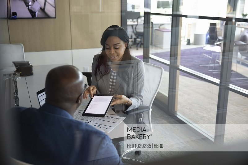 Businesswoman with digital tablet talking to client
