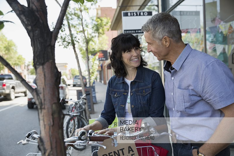 Smiling couple renting bicycle