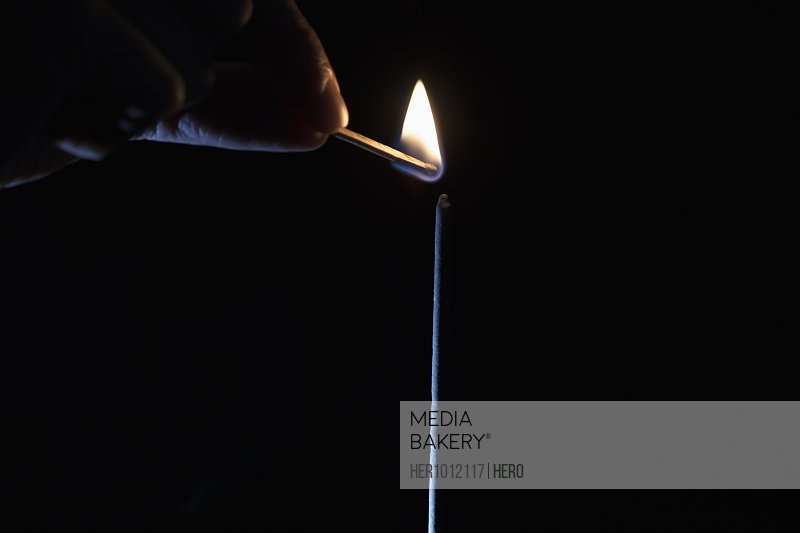 Hand sparking inspiration matchstick flame on black background