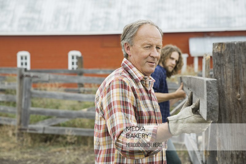 Father with son adjusting fence plank on farm
