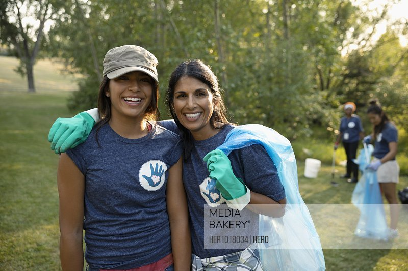 Portrait smiling mother and daughter volunteering, cleaning up garbage in park