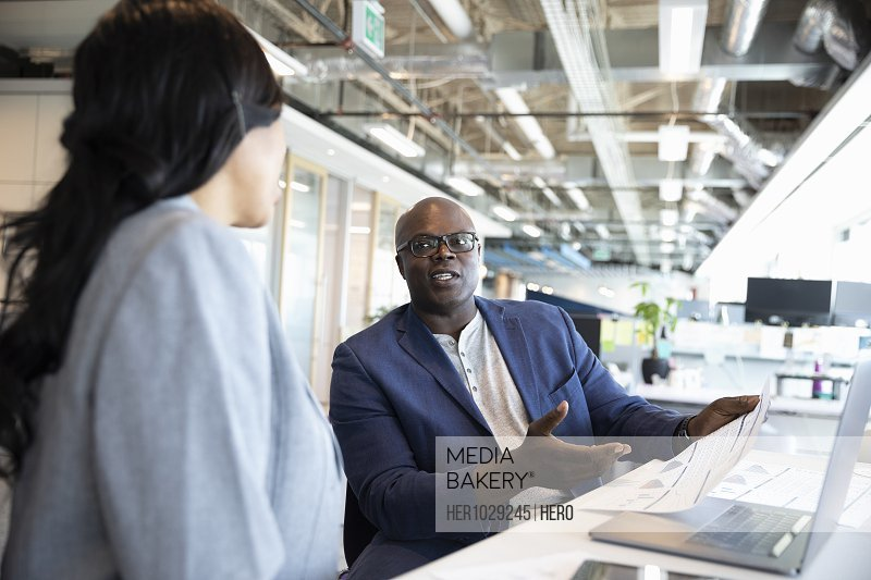 Businessman with plans talking to female colleague