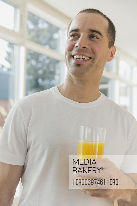 Man smiling as he holds a glass of orange juice