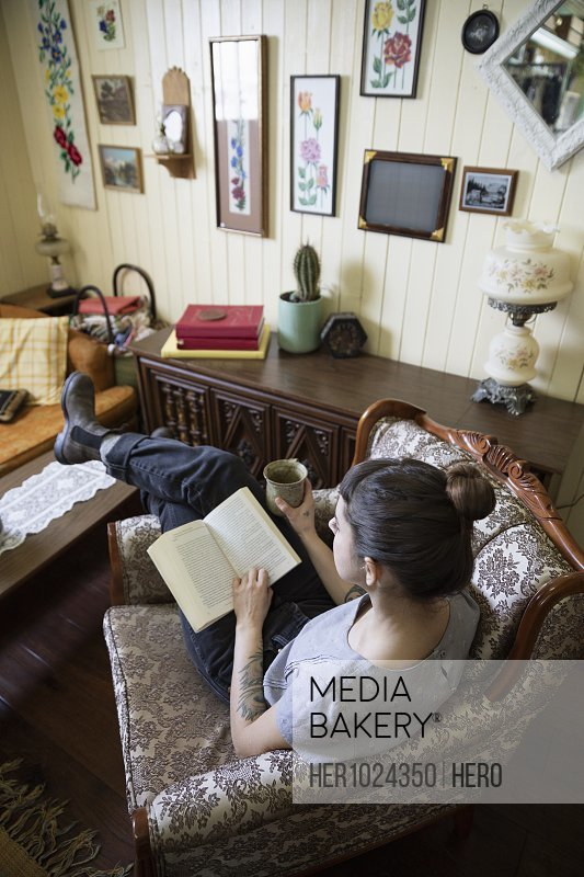 Woman reading book and drinking coffee in living room