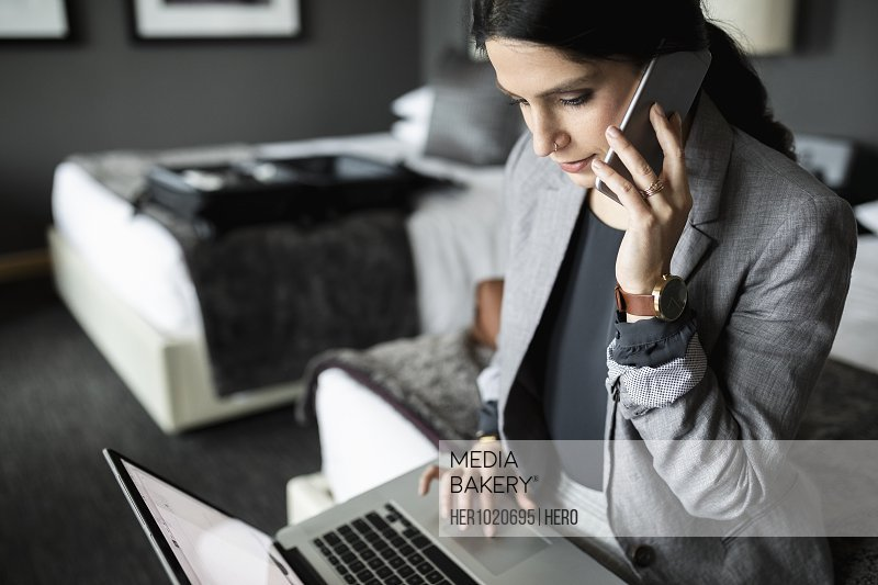 Businesswoman talking on smart phone and working at laptop in hotel room