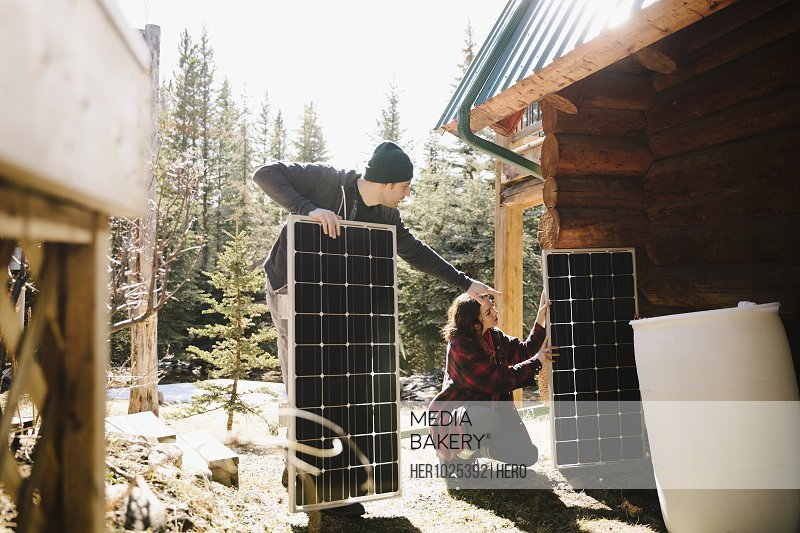 Couple installing solar panels outside cabin