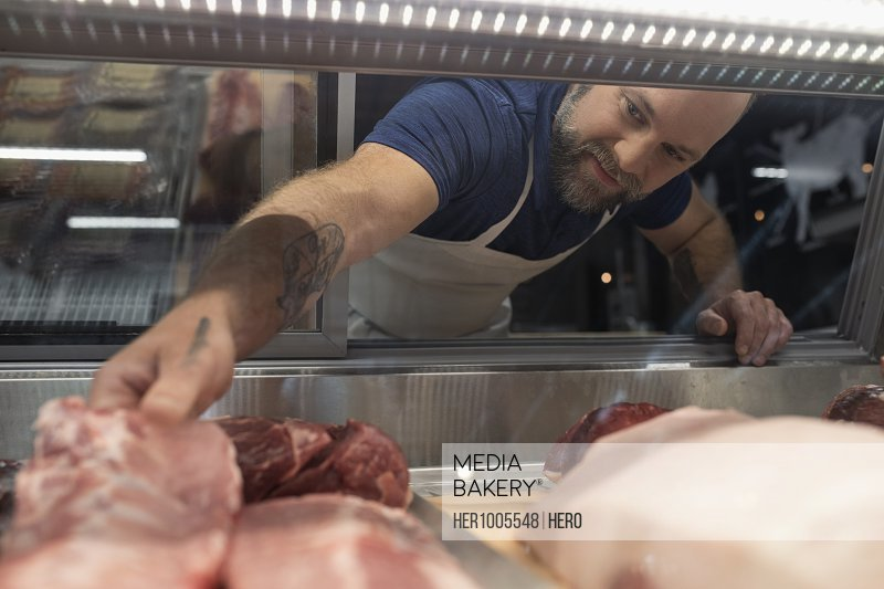 Male butcher reaching for raw meat in display case in butcher