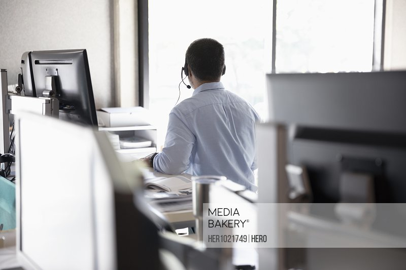 Businessman with headset working in cubicle
