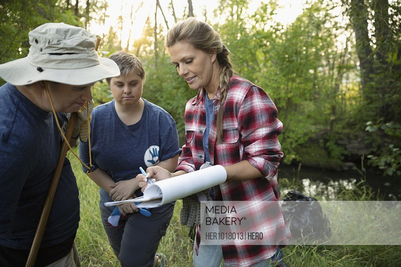 Woman with clipboard talking to people volunteering, cleaning up garbage in woods