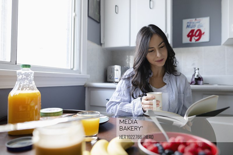 Young Latinx woman reading book and drinking coffee in morning kitchen
