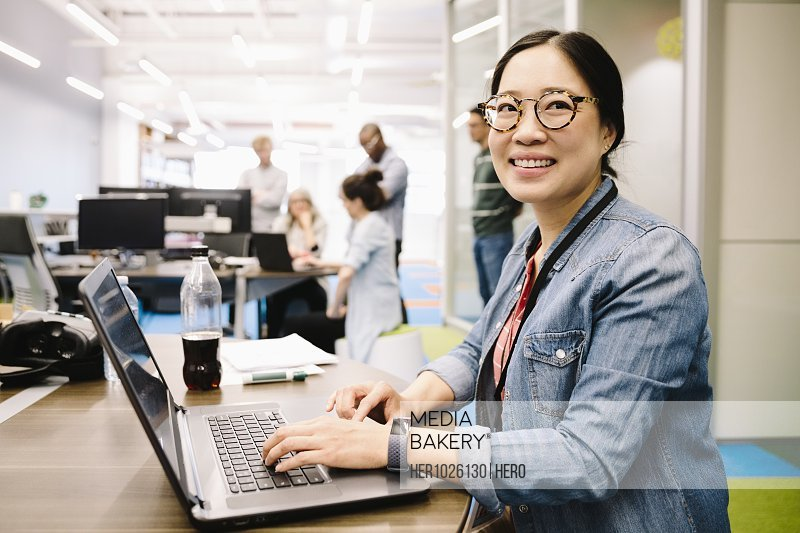 Portrait smiling, confident creative businesswoman using laptop in open plan office