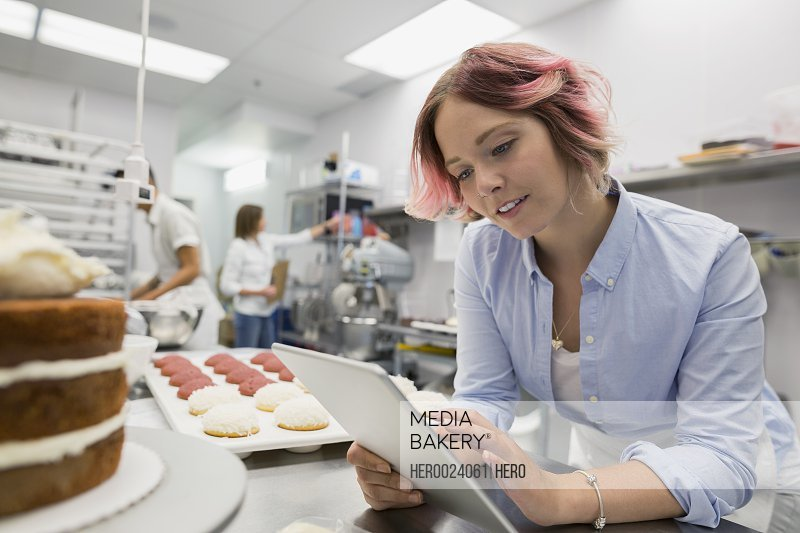 Pastry chef with digital tablet in commercial kitchen