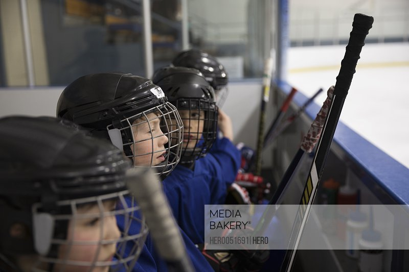 Boy ice hockey players in helmets watching game on bench