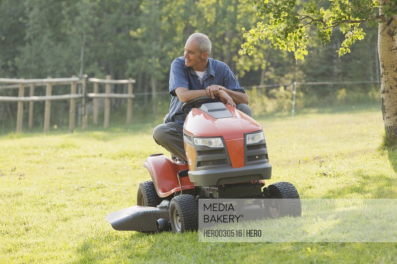 middle-aged man sitting on riding mower