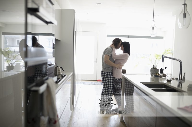Affectionate, romantic couple in pajamas kissing in morning kitchen