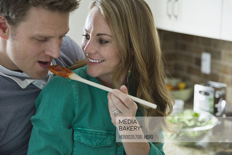 Woman offering husband a taste test from spoon.