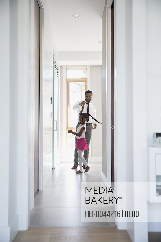 Father spinning daughter dancing in hallway