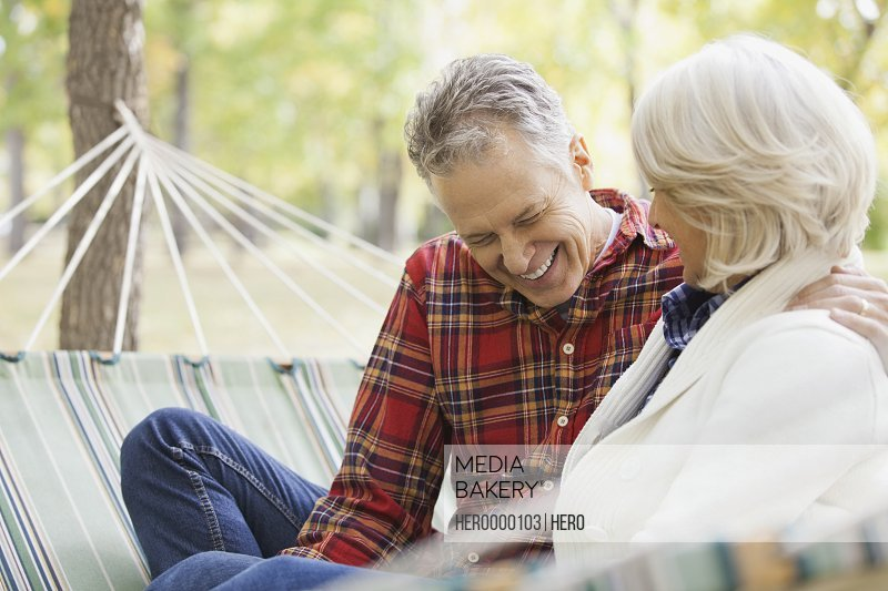 Happy mature couple sitting in hammock at park during autumn