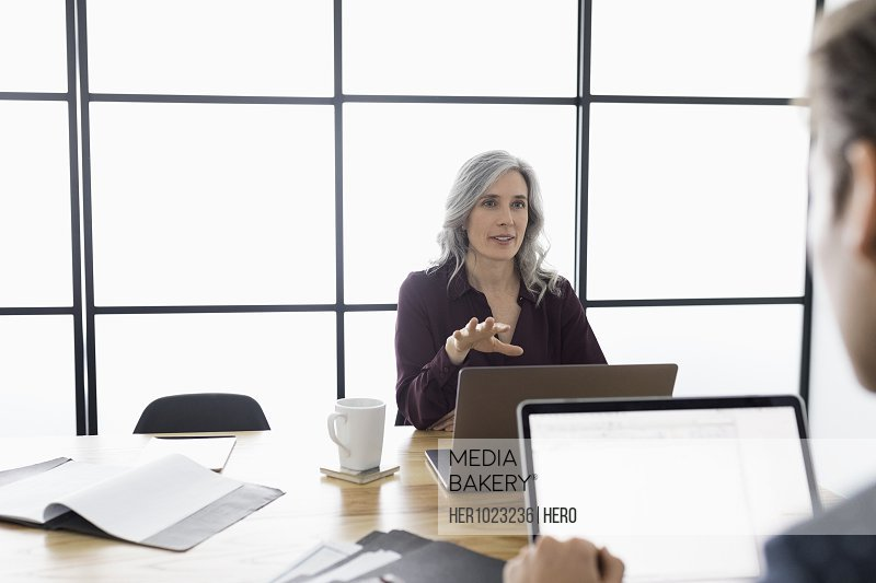 Businesswoman talking at laptop in conference room meeting
