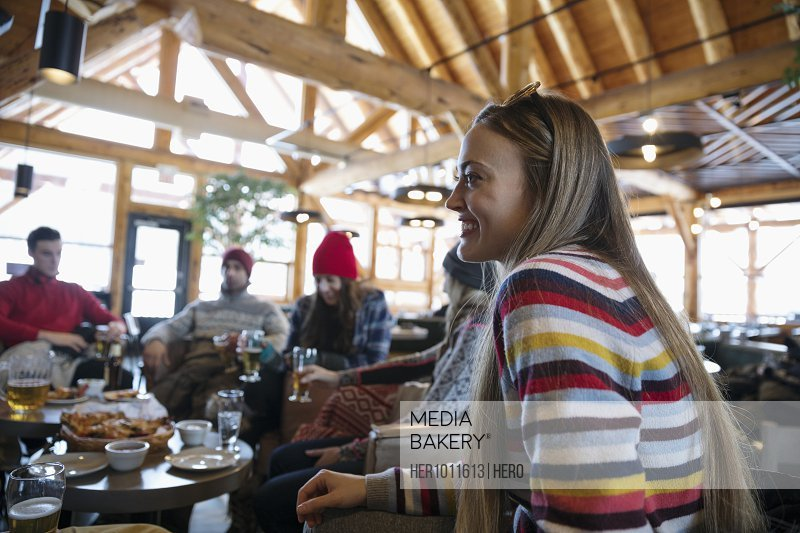 Smiling young woman enjoying apres-ski with friends in ski resort lodge