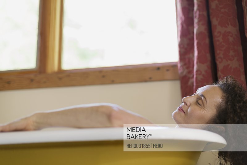 middle aged woman relaxing in bathtub