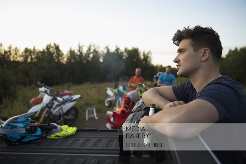 Pensive young man drinking beer at truck bed near friends and motorbikes