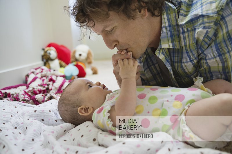 a533207cf Mediabakery - Photo by Hero Images - Father kissing baby girls hand