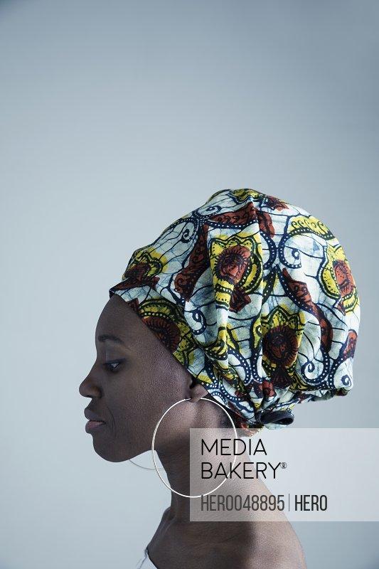 Profile portrait serious African American woman wearing gele headscarf and large hoop earrings