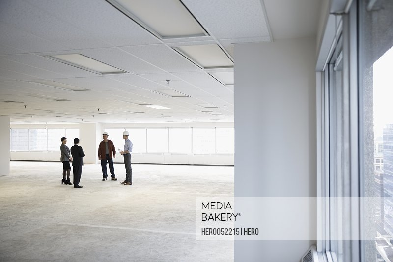 Contractor and architects talking in unfinished empty open plan office
