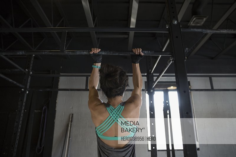 Woman doing pull-ups at gym