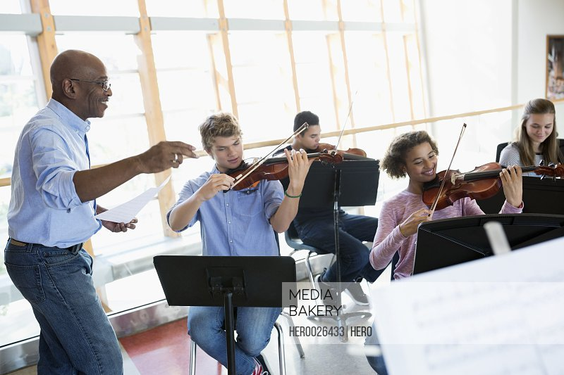 High school teacher leading music class