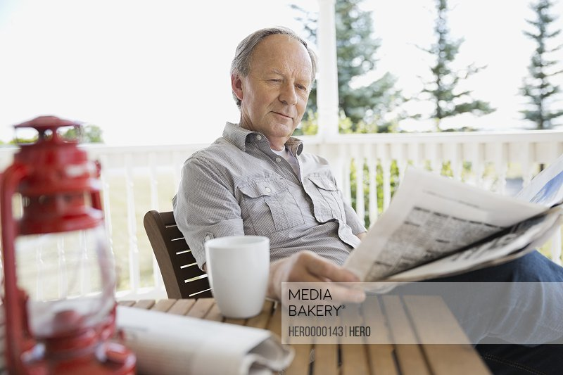 Senior man reading newspaper on porch