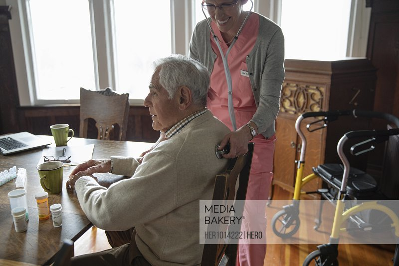 Home caregiver using stethoscope on senior man at dining table