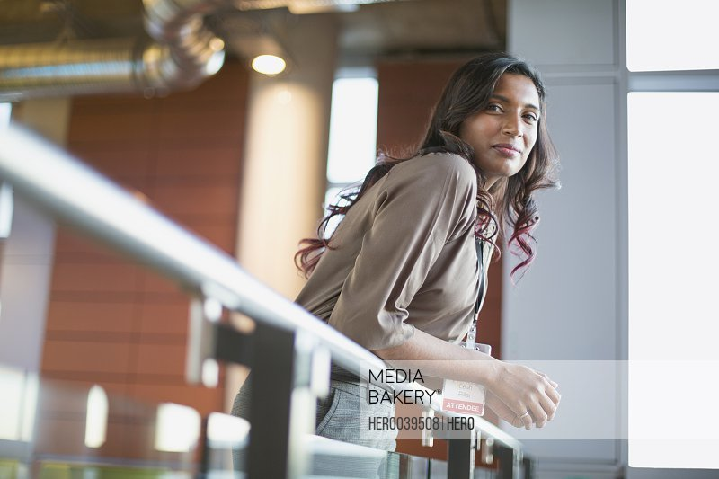 Pretty woman with conference badge leaning on railing