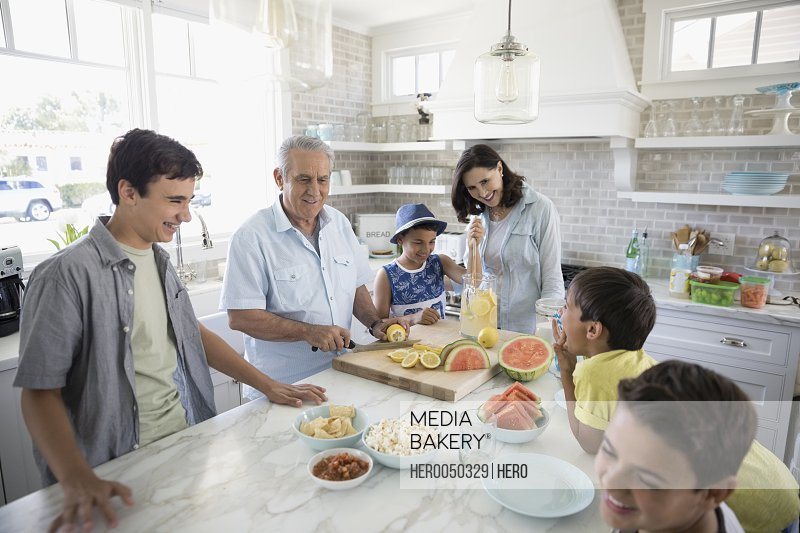 Multi-generation family making lemonade and snacking in kitchen