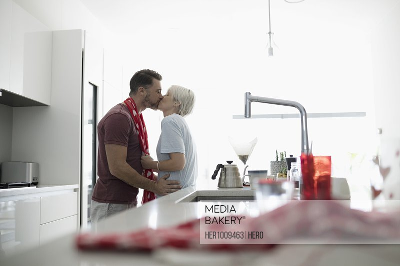 Affectionate, romantic couple kissing in morning kitchen