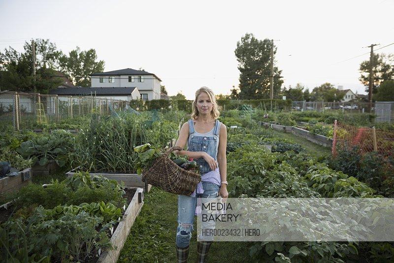 Portrait woman overalls basket harvested vegetables garden