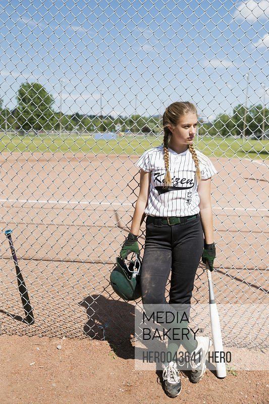 Middle school girl softball player with batting helmet and bat leaning on sunny fence