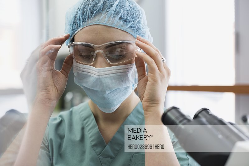 Female medical technician putting on protective goggles