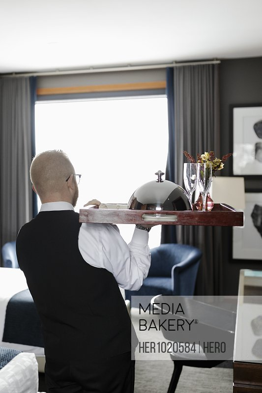 Male room service hotel staff waiter serving food on tray in hotel room